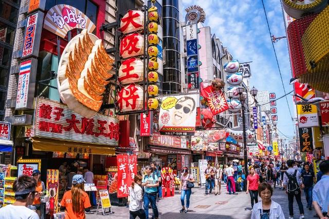 Tourists walking around crowded and busy Dotonbori Arcade, the center of Minami area of Osaka, Japan.