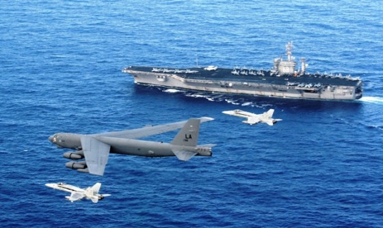96th Expeditionary Bomb Squadron as it flies past the aircraft carrier